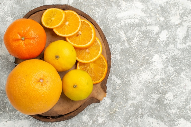 Vue de dessus des oranges fraîches avec des mandarines sur le fond blanc agrumes fruits frais tropicaux exotiques