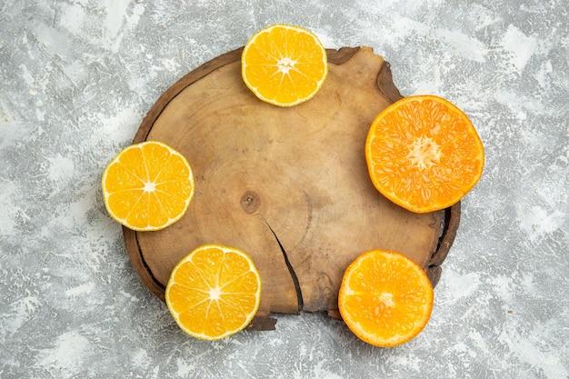 Vue de dessus des oranges fraîches tranchées sur une surface blanche jus d'agrumes fruits frais mûrs