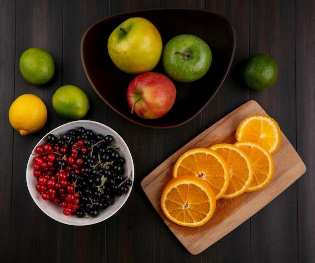 Vue de dessus des oranges hachées sur une planche avec des groseilles rouges et noires dans un bol avec des pommes sur une surface en bois
