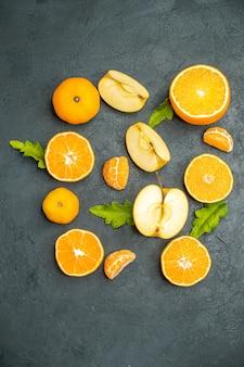 Vue de dessus des oranges et des pommes coupées sur fond sombre