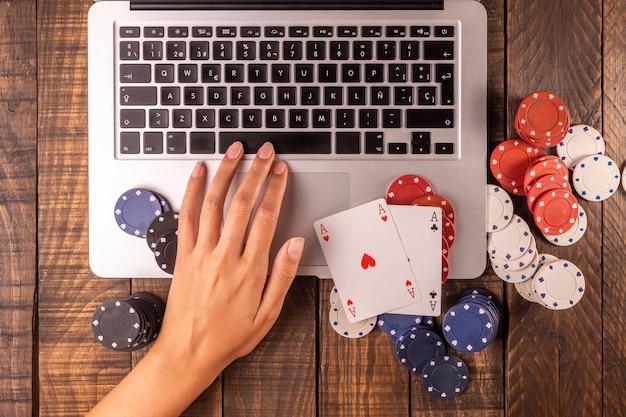 Vue de dessus d'un ordinateur avec des jetons de poker et des cartes pour parier ou jouer.