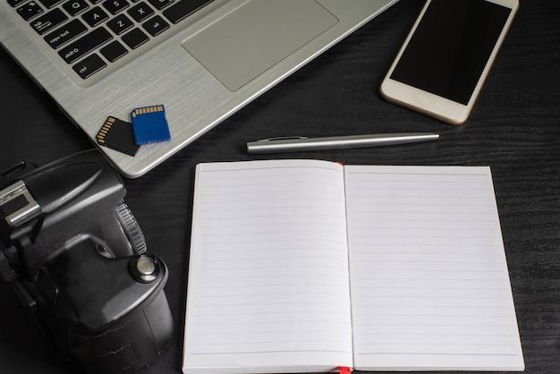 Vue de dessus ordinateur portable, appareil photo, smartphone, ordinateur portable, stylo, carte mémoire