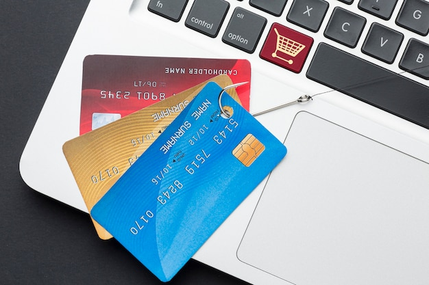 Vue de dessus de l'ordinateur portable avec carte de crédit et hameçon