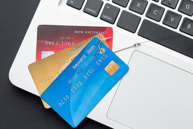 Vue de dessus d'un ordinateur portable avec des cartes de crédit et un crochet pour le phishing