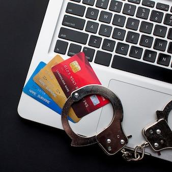 Vue de dessus d'un ordinateur portable avec des cartes de crédit et des menottes