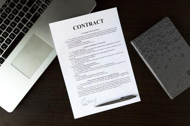 Vue de dessus de l'ordinateur portable, contrat, planificateur et stylo argenté sur table en bois au bureau