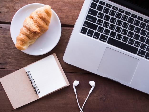 Vue de dessus de l'ordinateur portable, écouteurs, cahier et croissant sur la table en bois.