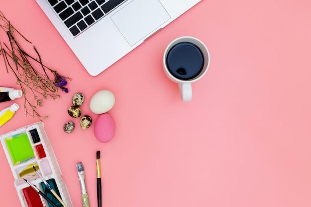 Vue de dessus ordinateur portable fond et peinture ensemble préparant pour pâques sur fond rose, oeufs de pâques