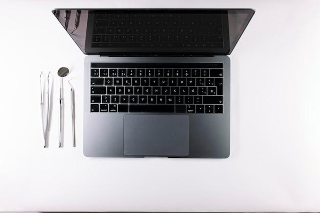Vue de dessus d'un ordinateur portable gris et des outils d'un dentiste