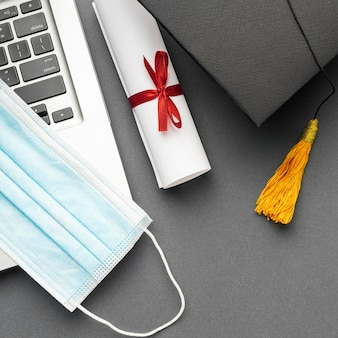 Vue de dessus de l'ordinateur portable avec masque médical et casquette académique