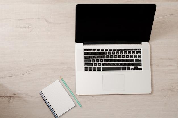 Vue de dessus d'un ordinateur portable et d'un ordinateur portable avec un crayon sur un fond en bois clair, espace pour le texte