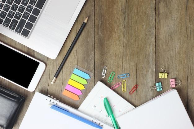 Vue de dessus ordinateur portable, smartphone, portefeuille, stylo, crayon et calendrier placés sur un bois marron.