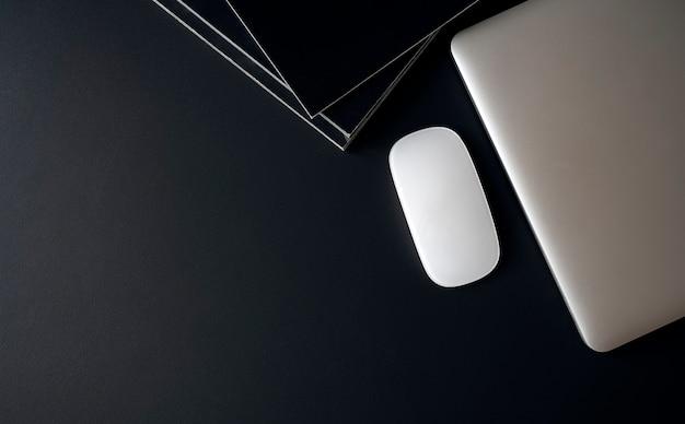 Vue de dessus de l'ordinateur portable avec souris et livres sur la table supérieure en cuir noir.