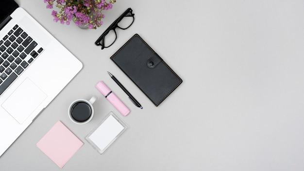 Vue de dessus d'un ordinateur portable avec une tasse de café et papeterie sur fond gris