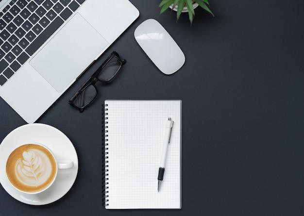 Vue de dessus avec ordinateur portable, téléphone portable, tasse à café, crayon, crayon et verres placés sur fond noir