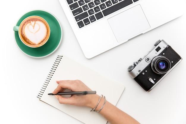 Vue de dessus d'un ordinateur portable, d'un vieil appareil photo, d'une tasse de café et d'une main de femme écrivant dans un ordinateur portable sur fond blanc