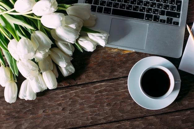 Vue de dessus des ordinateurs portables et des tulipes sur un fond en bois
