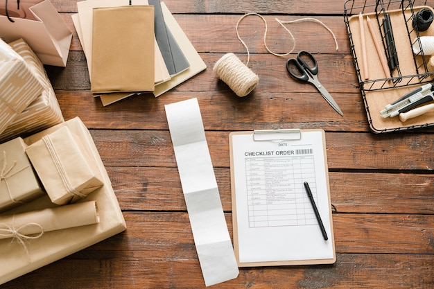 Vue de dessus de l'ordre de la liste de contrôle avec un stylo entouré de cadeaux emballés et d'articles d'emballage sur table en bois