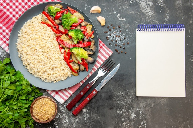 Vue de dessus de l'orge perlé avec de délicieux légumes cuits et des couverts sur une table grise à l'huile de riz couleur repas photo vie saine régime alimentaire
