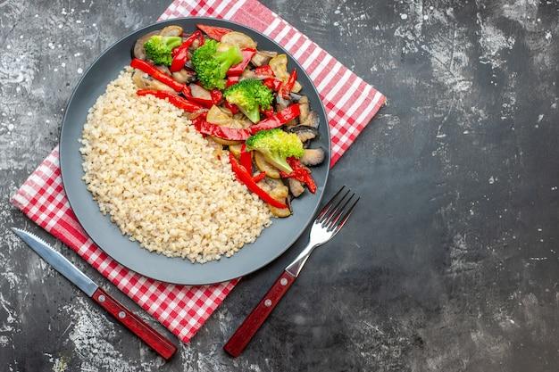 Vue de dessus de l'orge perlé avec de délicieux légumes cuits sur une table grise
