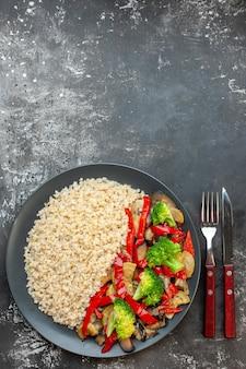 Vue de dessus de l'orge perlé avec de savoureux légumes cuits sur un bureau gris