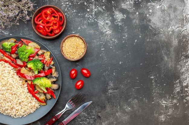 Vue de dessus de l'orge perlé avec de savoureux légumes cuits sur la table grise