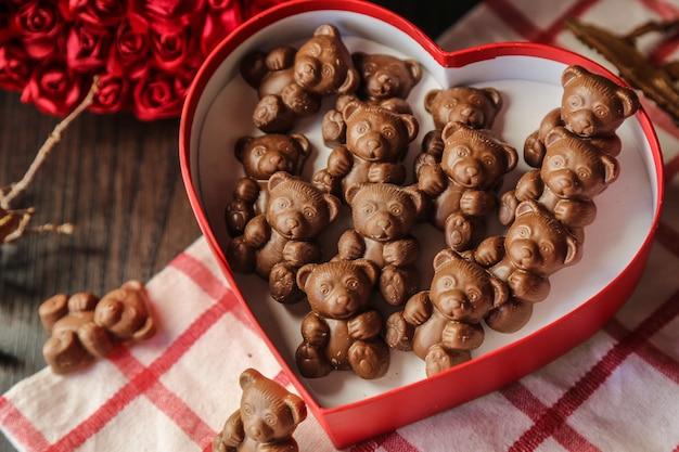 Vue de dessus des ours en chocolat dans une boîte en forme de coeur rouge