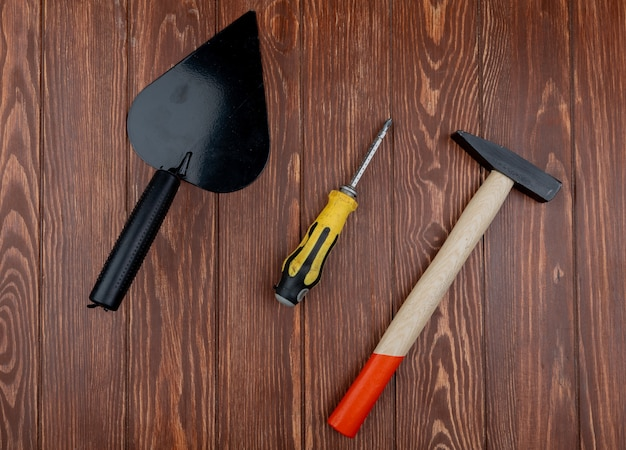 Vue de dessus des outils de construction comme truelle de tournevis et marteau en brique sur fond de bois