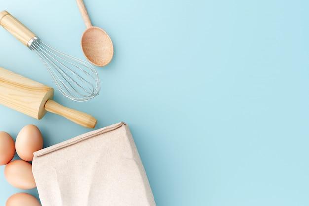 Vue de dessus outils de cuisson sur fond bleu pastel.