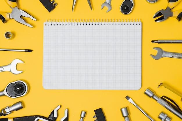 Vue de dessus des outils sur fond jaune. pince, clés ouvertes, tournevis et agrafeuse à plat avec espace de copie.