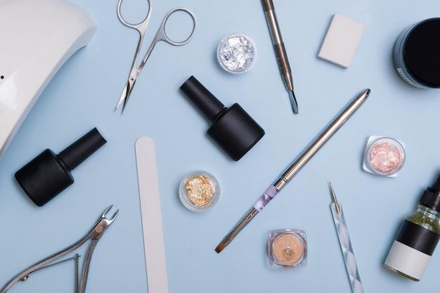 Vue de dessus des outils et des matériaux pour la manucure moderne et l'extension des ongles sur une surface bleue