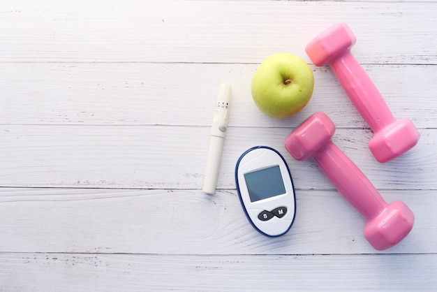 Vue de dessus des outils de mesure diabétique, pomme et haltère sur table.