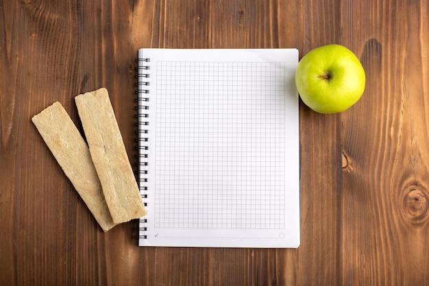 Vue de dessus ouvrir le cahier bleu avec des craquelins et pomme verte sur le bureau marron
