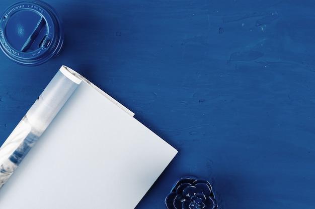 Vue de dessus de la page du magazine ouvert avec copie espace sur table bleu classique