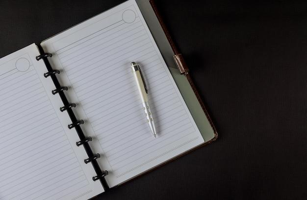 Vue de dessus avec une page vierge de cahier est au milieu du bureau de l'espace de travail