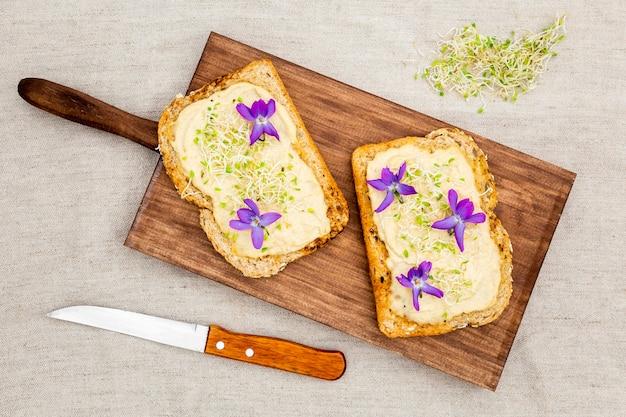 Vue de dessus de pain grillé avec des fleurs sur une planche à découper