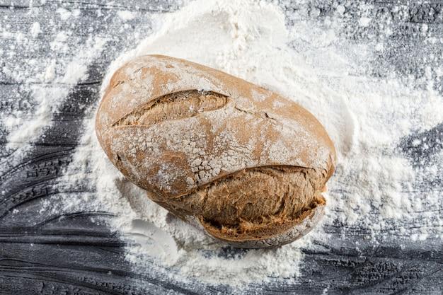 Vue de dessus de pain sur une surface en bois sombre farineuse
