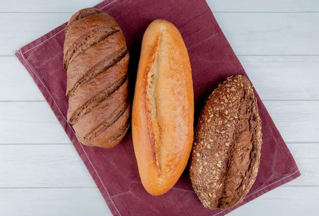 Vue de dessus des pains comme baguette vietnamienne et noire et pain noir sur tissu bordo et table en bois