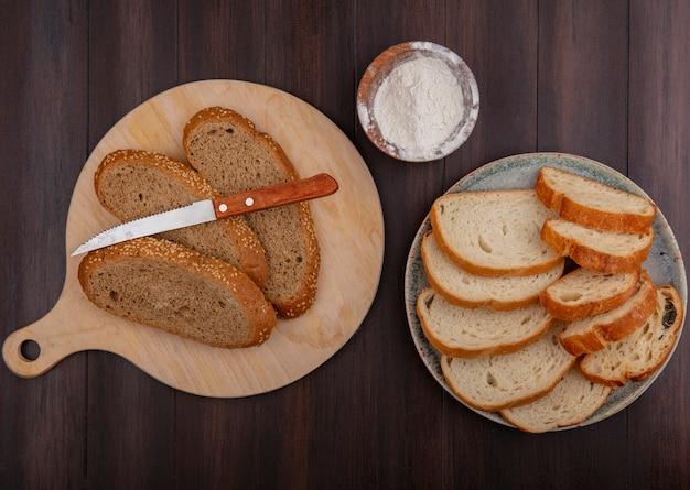Vue de dessus des pains comme des tranches de pain baguette en épi brun avec un couteau sur une planche à découper et dans une assiette et de la farine sur fond de bois