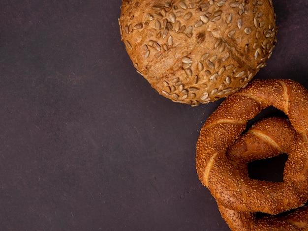 Vue de dessus des pains en épi et bagel turc sur le côté droit et fond marron avec copie espace