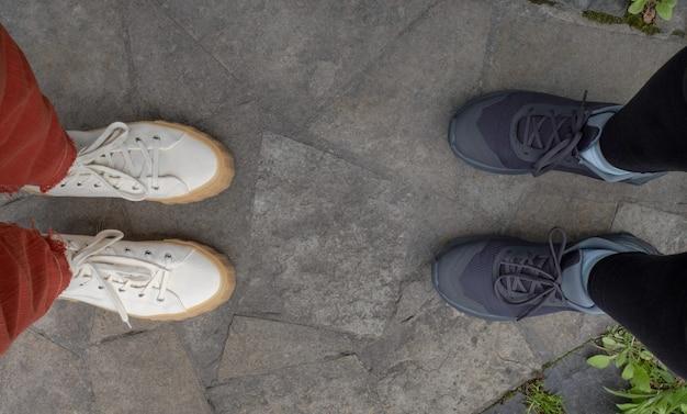 Vue de dessus d'une paire de baskets blanches et grises pour hommes et femmes sur le sol