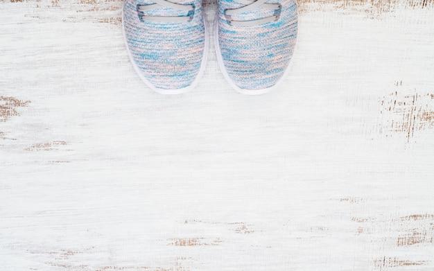 Vue de dessus de la paire de baskets de sport tendance sur fond de bois blanc gruge.