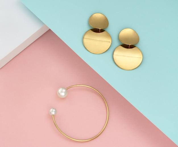 Vue de dessus de la paire de boucles d'oreilles et bracelet doré avec perles sur papiers couleurs pastel
