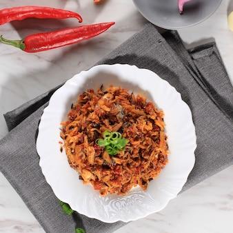 Vue de dessus pampis tongkol, plat de fruits de mer traditionnel de manado composé de poisson râpé épicé, servi sur céramique blanche
