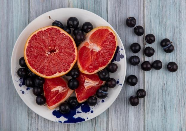 Vue de dessus pamplemousse coupé en deux avec prune cerise sur une plaque sur fond gris