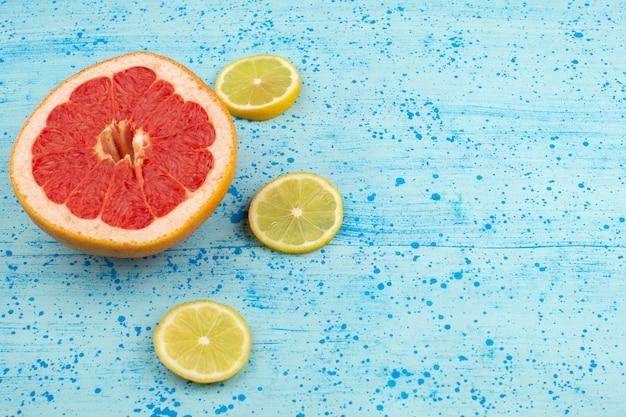 Vue de dessus de pamplemousses et de citrons en tranches mûres moelleuses sur le fond bleu vif
