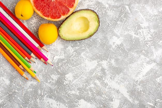 Vue de dessus pamplemousses frais agrumes moelleux et juteux avec des crayons sur une surface blanche