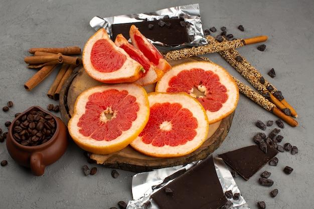 Vue de dessus des pamplemousses en tranches anneau frais moelleux juteux avec des bâtons de chocolat et des graines de café sur le sol gris