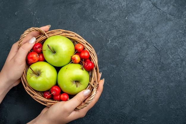 Vue de dessus panier avec fruits pommes et cerises douces sur arbre de fraîcheur de composition de baies de fruits de surface gris foncé