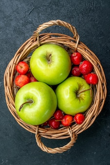 Vue de dessus panier avec fruits pommes et cerises douces sur arbre de fraîcheur de composition de baies de fruits de surface sombre